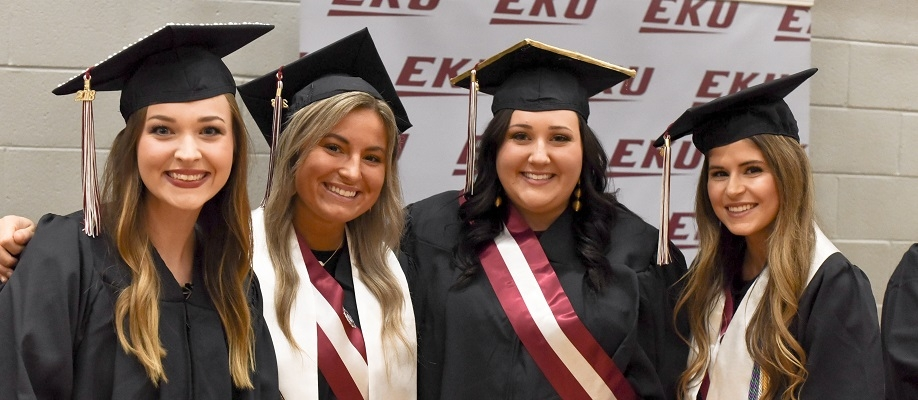 EKU graduates in cap and gowns smile in front of EKU backdrop